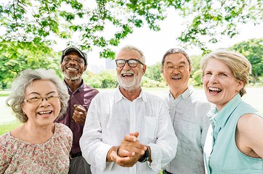 A photo of five seniors enjoying time outside.